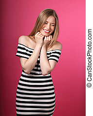 Beautiful toothy laughing blond woman in striped dress with hands under the face on pink background.