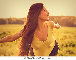 Beautiful toothy natural smiling relaxing woman wanting to fly and looking happy with long amazing hair on nature bright sunset summer background. Closeup