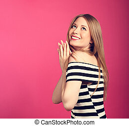 Beautiful toothy smiling blond long stright hairstyle woman in love dreaming and looking up waiting the gift on pink background
