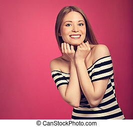 Beautiful toothy smiling blond woman in striped dress with hands under the face on pink background. Toned closeup portrait