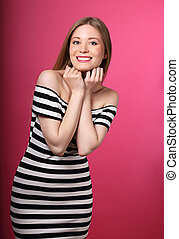 Beautiful toothy smiling blond woman in striped dress with hands under the face on pink background.