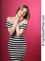 Beautiful toothy smiling positie blond woman in striped dress with hands under the face on pink background. Closeup portrait