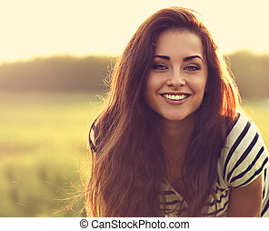 Beautiful toothy smiling young woman looking happy with long amazing bright hair on nature bright sunset summer background. Closeup toned color portrait