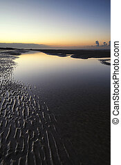 Beautiful tranquil sunrise over low tide beach