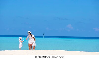Beautiful tropical beach landscape with family in white enjoying summer vacation