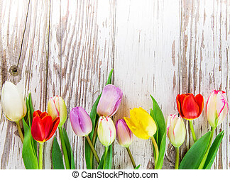 Beautiful tulips background on wooden table.