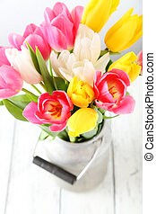 Beautiful tulips in can on white wooden background