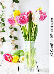 Beautiful tulips in vase on white wooden background