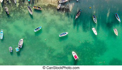 Beautiful turquoise ocean water with boats on the water. Top view aerial photo