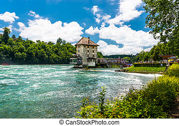 Beautiful, turquoise Rhine river flowing from a waterfall in northern Switzerland. Waterfall on the river Rhine. Visible boat and old castle on a small island.