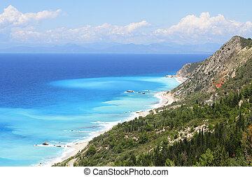 Beautiful turquoise sea and coastal hills with trees on the isla