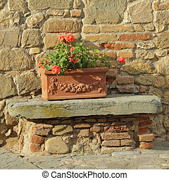 beautiful tuscan terracotta planter in front of old stone and brick house, Italy, Europe