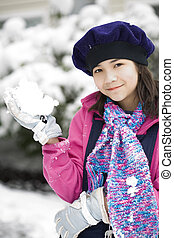 Beautiful twelve year old girl playing in the snow in winter