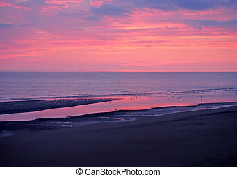 beautiful twilight dramatic purple sky over the sea with colourful evening clouds reflected in calm water and dark beach