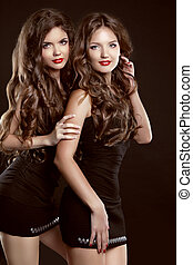 Beautiful two Young women with long healthy wavy hair...