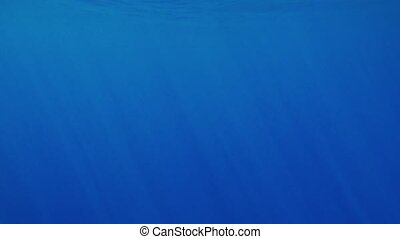 Beautiful under water video of dark blue sea water and sun...