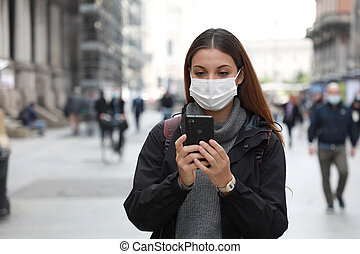 Beautiful university student woman wearing surgical mask using her mobile phone while walking in the street