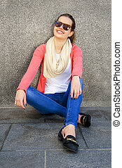 Beautiful urban woman, girl siting by the wall in city with sunglasses