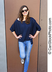 Beautiful urban woman, girl standing by the wall in city wering jeans