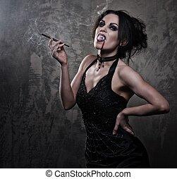 Beautiful vampire woman in black dress smoking