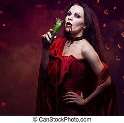 Beautiful vampire woman in red dress drinking