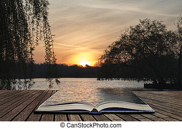 Beautiful vibrant Spring sunrise over calm lake in English countryside concept coming out of pages in open book
