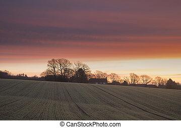 Beautiful vibrant Winter sunrise over farmhouse in English countryside landscape