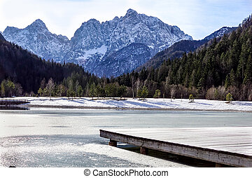 Beautiful view at sunset of the peaceful lake Fucine Tarvisio, Italy with green forest and snowy mountains in the background .