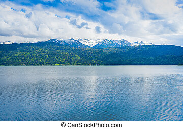beautiful view from a lake to the mountains in bavaria partly covered in snow