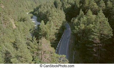 Beautiful view from above car moving along road among green forest to mountains