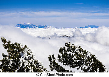 Beautiful view from high above the clouds towards the summit of Mt San Gorgonio and Mt San Jacinto, visible in the background; photo taken from Mount San Antonio (Mt Baldy), Los Angeles county
