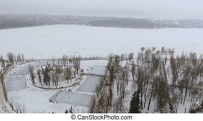 Beautiful view from the air to a winter park and a frozen lake. People relax in the open air, skate, fishermen catch fish.