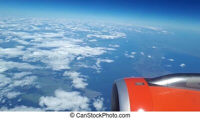 Beautiful view from the airplane window to the blue sky and white clouds, white clouds float above the ground