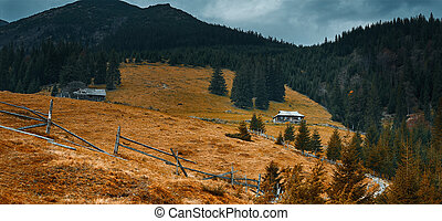 beautiful view of a autumn mountain landscape with wooden cottages on the mountain slope, and dramatic cloudy sky over mountains at evening