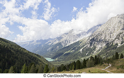 Beautiful view of alpine mountain range, valley and lake, Italy.