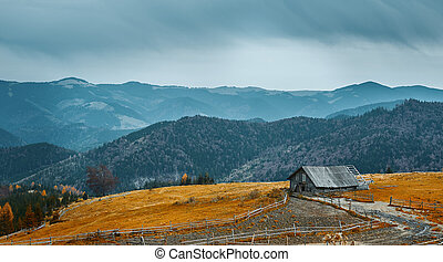 beautiful view of an autumn mountain landscape with a cloudy sky and farm