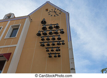 Beautiful view of big clock on the wall of yellow building with set of bells underneath. Willemstad, Curasao.