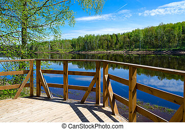 Beautiful view of forest on bank of Western Dvina river with reflection in water