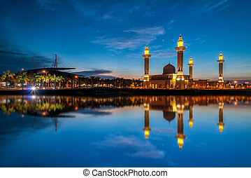Beautiful view of mosque by the lakeside with full reflection during blue hour in the morning.