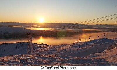 Beautiful view of moving cable car in snow-covered mountaines at sunset time. Sweden