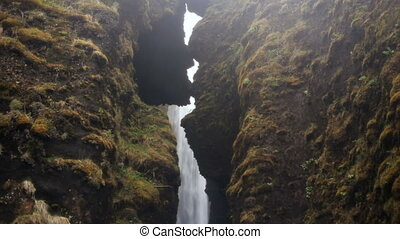 Beautiful view of powerful waterfall Gljufrabui in Iceland. Water falling down from the cliff and splashing, rainy day.