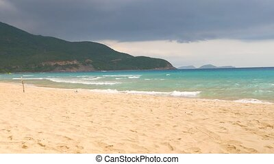 Beautiful view of sandy beach and waving blue sea water with stormy sky in the background