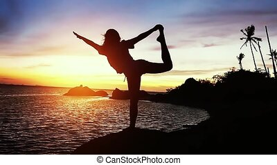Beautiful view of silhouette of young woman doing yoga stretching on the rock with sea view at sunset. slow motion.