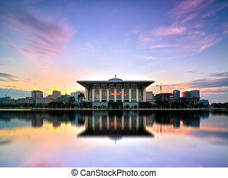 Beautiful view of Sultan Mizan Zainal Abidin Mosque (Iron Mosque) in Putrajaya, Malaysia during sunrise with full reflection.