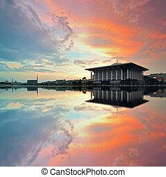 Beautiful view of Sultan Mizan Zainal Abidin Mosque (Iron Mosque) in Putrajaya, Malaysia during sunrise with full reflection.