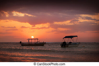 Beautiful view of sunset on the beach. Boats in a sunlight.