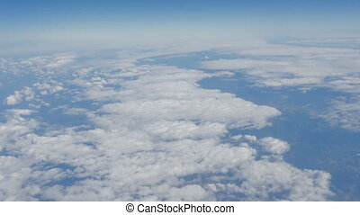 Beautiful view of the blue sky with clouds from the porthole of the plane during the flight