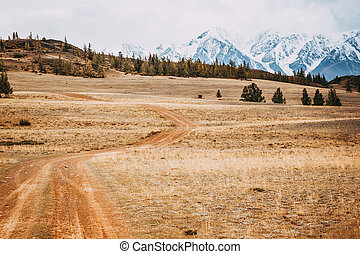 Beautiful view of the hills with a dirt road to the snowy peaks. Colorful mountain valley with rocks.