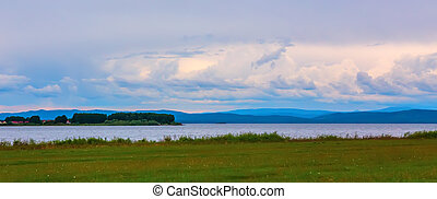 view of the lake with an island and a cloudy sky