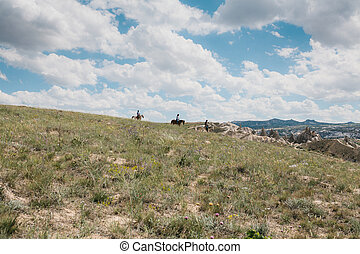 Beautiful view of the landscape of Cappadocia in Turkey. Ahead is a beautiful blue sky with clouds. Hills and riders on horses in the distance.